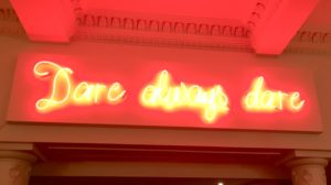 A photo of neon sign saying 'Dare always dare' in The Old Vic theatre in london