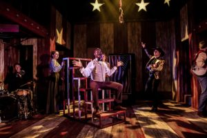 Production photo showing Eddie Elliott in Assassins at The Watermill Theatre
