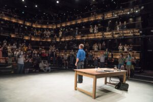 Photo of Ralph Fiennes facing the audience at the Bridge Theatre at the end of a peformance of David Hare's Beat The Devil